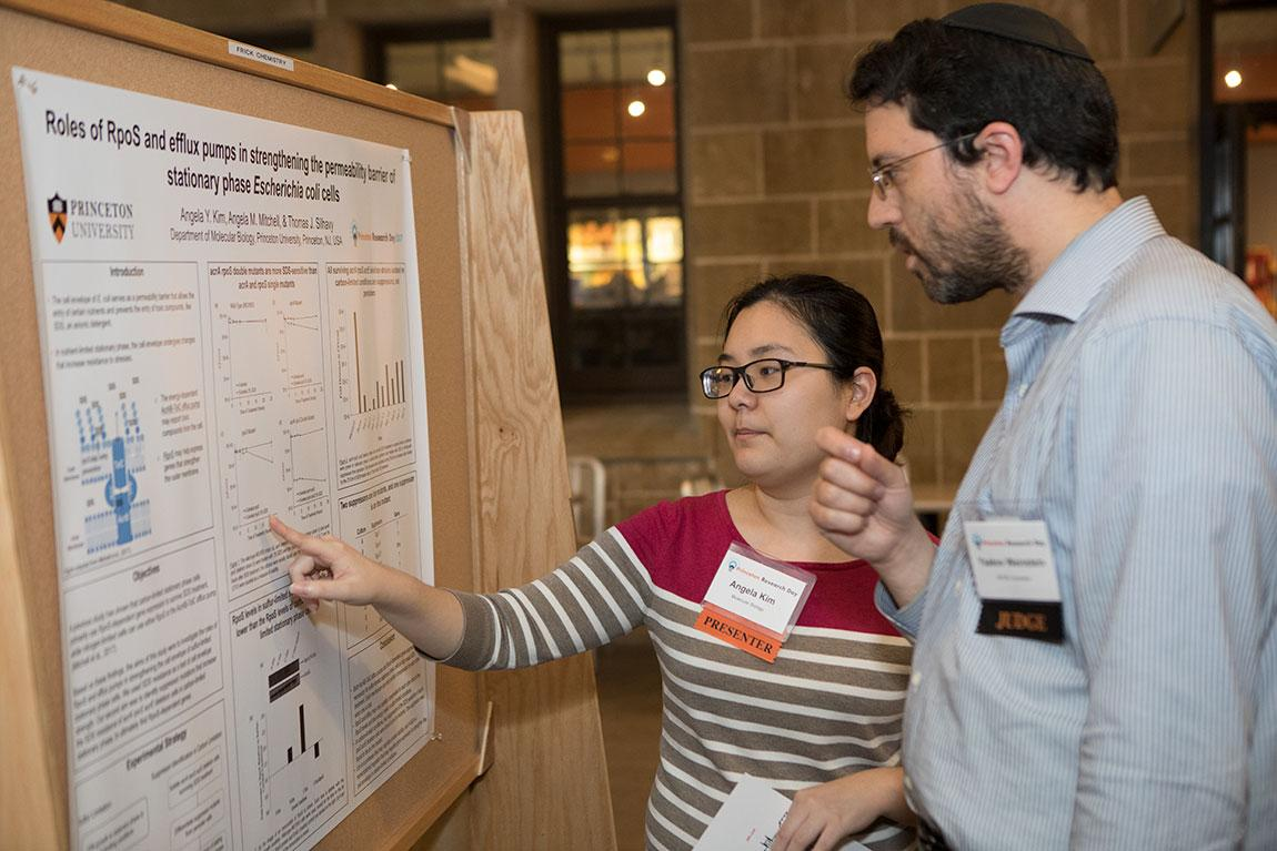 """Senior Angela Kim, who is majoring in molecular biology, discusses her poster, titled """"Roles of RpoS and Efflux Pumps in Strengthening the Permeability Barrier of Stationary Phase Escherichia Coli Cells,"""" with judge Yaakov Weinstein."""
