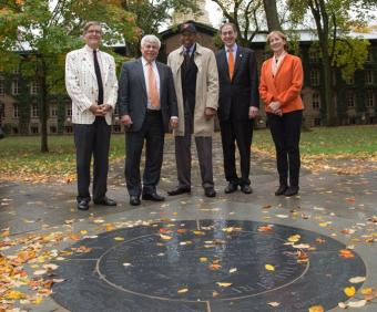 Alumni, Princeton University president and vice president and secretary stand near new medallion in front of Nassau Hall.