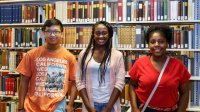 Interns stand in front of library book shelves